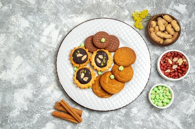 Vista dall'alto diversi biscotti dolci con noci su superficie bianca