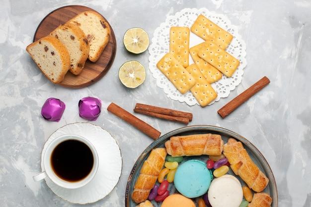 Vista dall'alto diversi dolci torte e caramelle con una tazza di tè su bianco