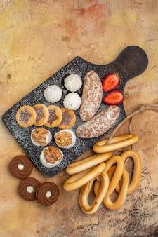 Vista dall'alto diversi dolci torte e biscotti sulla scrivania in legno