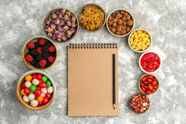Вид сверху разные сладости, конфеты, изюм и орехи на белом фоне, конфеты, сахар, печенье, печенье