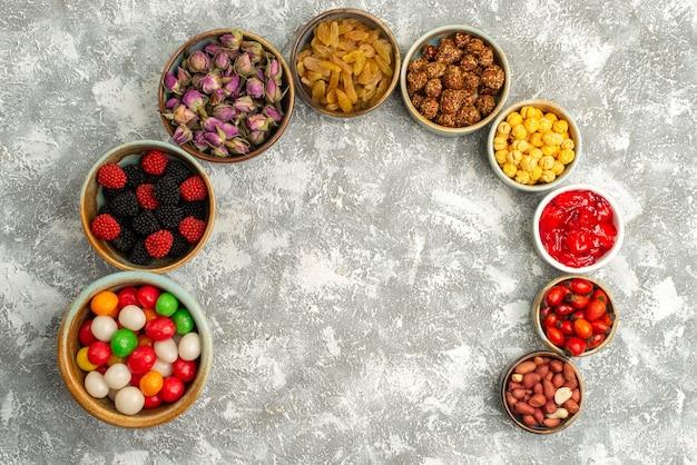 上面図白い背景の上のさまざまなお菓子キャンディーレーズンとナッツキャンディーシュガーグッディビスケット