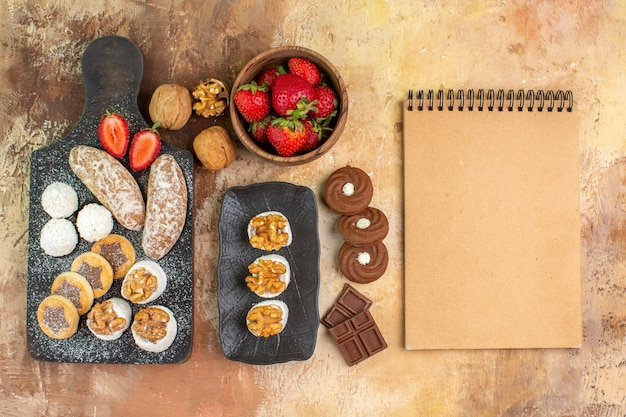 가벼운 책상에 쿠키와 과일이있는 다른 과자를 봅니다.