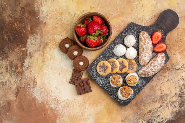 Vista dall'alto diversi dolci con biscotti e frutta sulla scrivania leggera