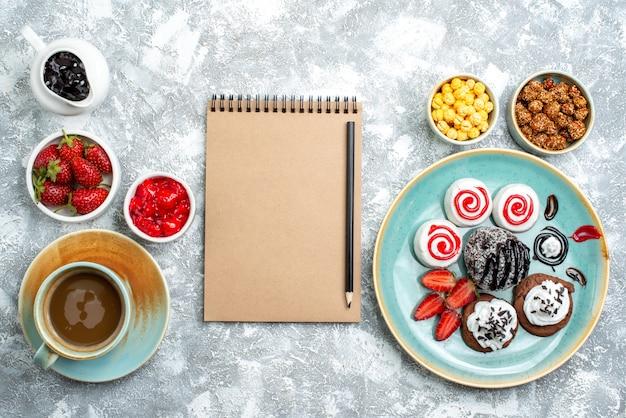 Вид сверху разные сладости с орехами, кофе и печеньем на белом пространстве
