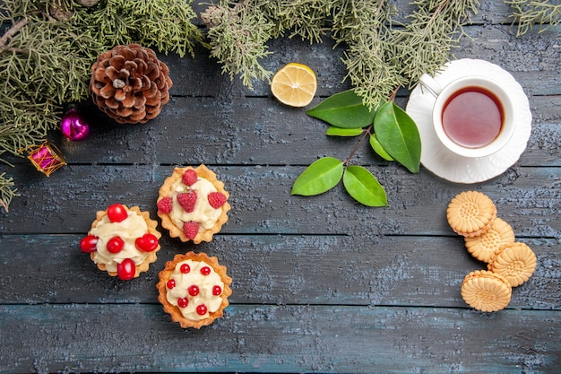 Top view different tarts cone fir-tree leaves christmas toys slice of lemon a cup of tea and biscuits on dark wooden table with copy space