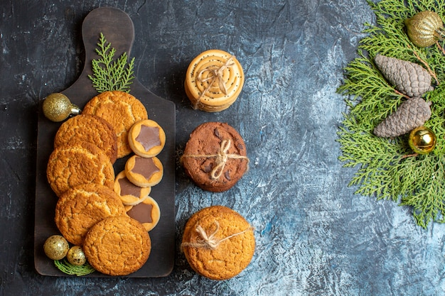 明るい暗いテーブルの上のさまざまなおいしいビスケットクリスマスの甘い新年のシュガークッキーティー