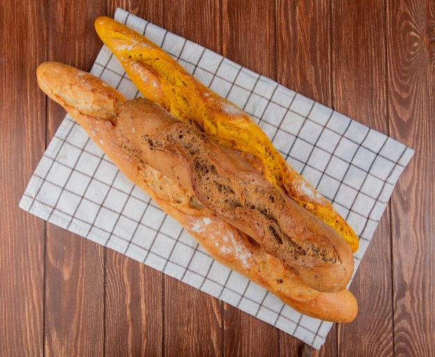 Top view of different types of baguette on plaid cloth and wooden background