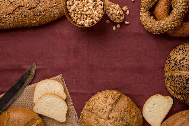 Vista superiore di diversi tipi di pane come bianco baguette bianco pannocchia con semi e coltello su sfondo bordeaux con spazio di copia