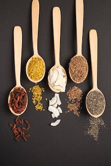 Top view of different types of natural superfoods in the wooden spoons on the black  background