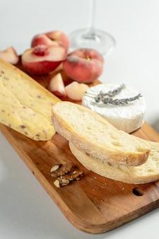 Разные виды сыров на деревянной разделочной доске. сыр с инжирным персиком, медом, чиабаттой и орехами, стакан красного вина. стильная еда квартира лежала на сером фоне. копировать пространство мягкий фокус