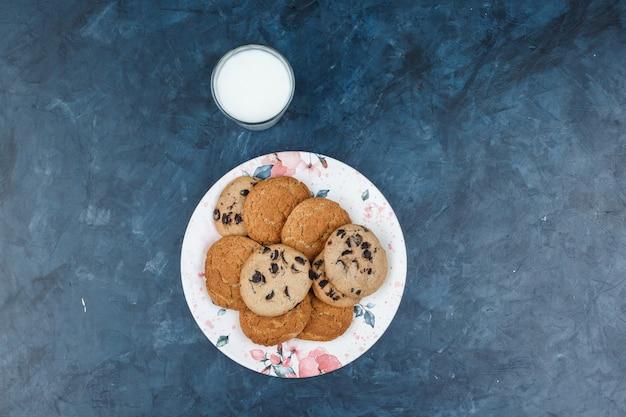 진한 파란색 대리석 배경에 우유와 함께 꽃 접시에 쿠키의 다른 유형을 볼 수 있습니다. 수평
