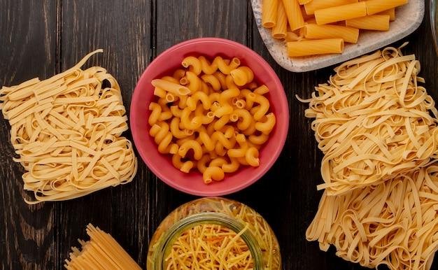 Vista dall'alto di diversi tipi di pasta come bucatini cavatappi spaghetti tagliatelle vermicelli e altri sulla superficie in legno