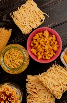 Top view of different types of pasta as bucatini cavatappi spaghetti vermicelli tagliatelle and others on wooden surface