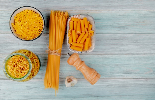 Top view of different types of pasta as tagliatelle spaghetti vermicelli ziti and others with garlic salt on wooden surface with copy space