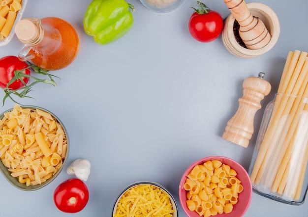 Vista dall'alto di diversi tipi di pasta come tagliatelle ziti pipe-rigate bucatini con pomodoro sale aglio pepe nero burro sulla superficie blu con spazio di copia