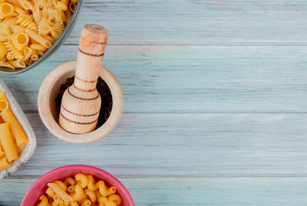Top view of different types of pasta as ziti fusilli and others with black pepper seeds in garlic crusher on wooden surface with copy space