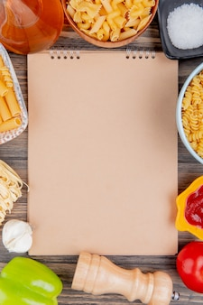 Top view of different types of pasta as ziti rotini tagliatelle and others with garlic melted butter salt tomato pepper and ketchup around note pad on wooden surface with copy space