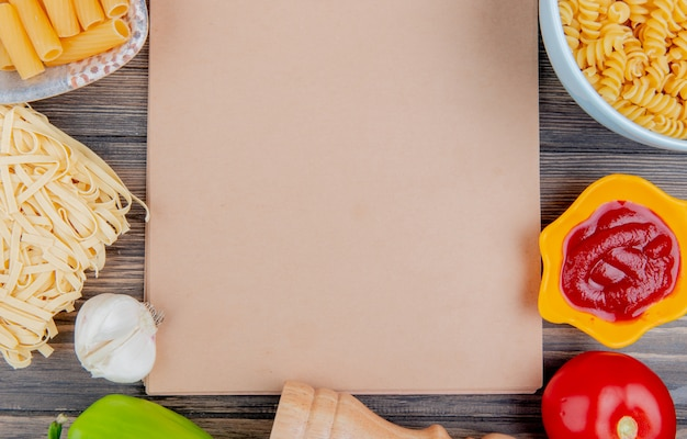 Top view of different types of pasta as ziti rotini tagliatelle and others with garlic tomato pepper and ketchup around note pad on wooden surface with copy space