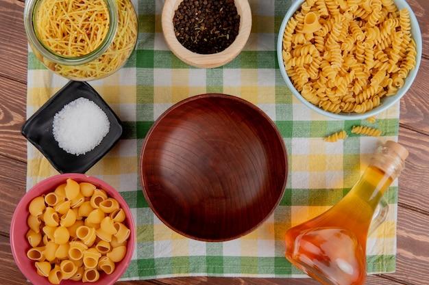 Vista dall'alto di diversi tipi di pasta in ciotole e barattolo sale pepe pepe nero intorno alla ciotola sul panno plaid e superficie in legno