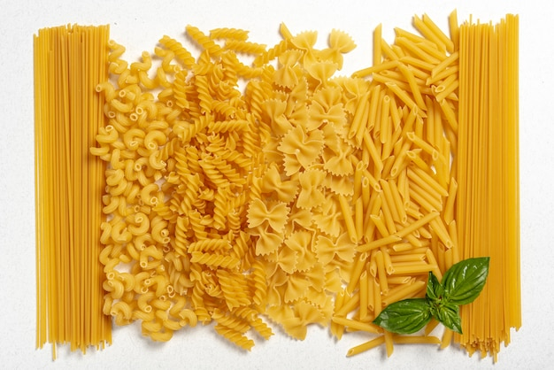 Top view of different types of pasta on plain background