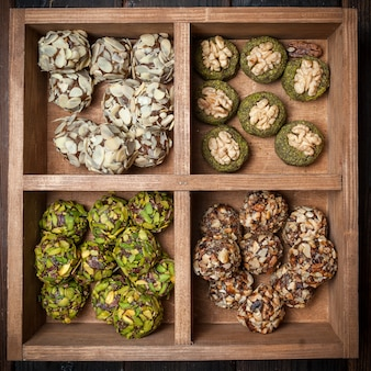 Top view different types of pistachio cookies in wooden box .