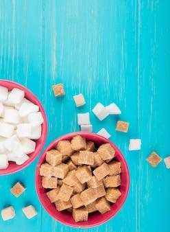 Vista superiore di diversi tipi di zollette di zucchero in ciotole su fondo di legno blu