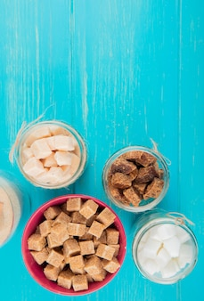 Top view of different types of sugar in glass jars on blue wooden background with copy space