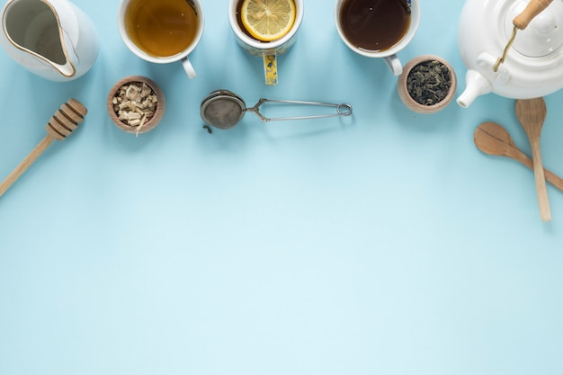 Top view of different types of tea; honey dipper; strainer; dry tea leaves; teapot on blue background