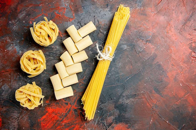 Top view of different types of uncooked pastas on black background