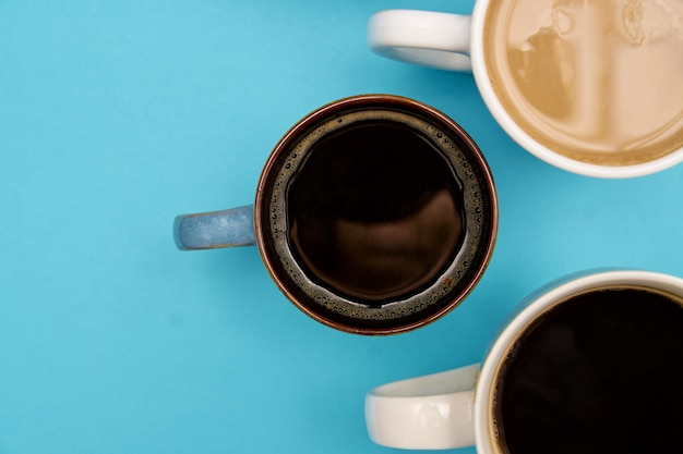 Top view of different typrs of hot coffe - black and with milk on a pastel blue background. banner with