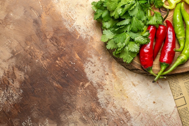 Top view different vegetables coriander hot peppers on round tree wood board a newspaper on amber background