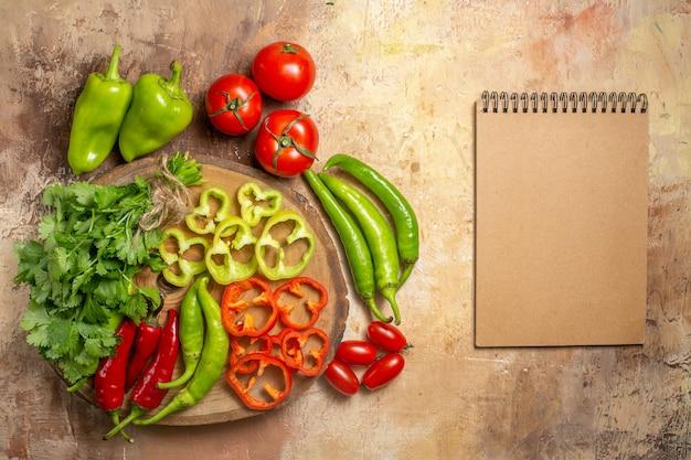 노란색 황토색 배경에 있는 둥근 나무 판자 체리 토마토에 다양한 야채를 잘게 썬 상위 뷰