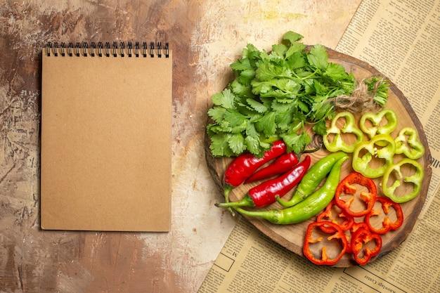 琥珀色の背景に丸い木の板に細かく切ったさまざまな野菜の上面図