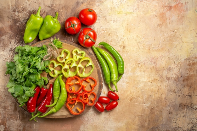 Top view different vegetables cut into pieces on round tree wood board cherry tomatoes on yellow ochre background