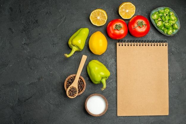 上面図さまざまな野菜レモンピーマンとトマトの暗い背景色サラダダイエット健康食品