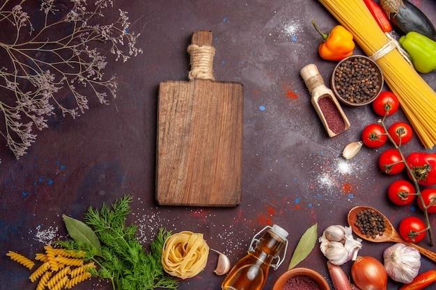 暗い背景の健康サラダ製品の色にさまざまな調味料でさまざまな野菜を上面図