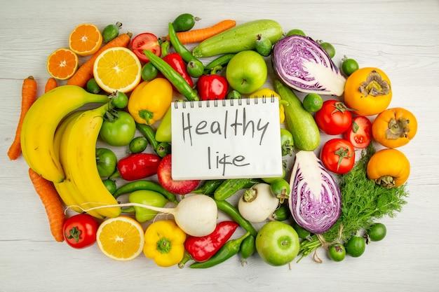 上面図白い背景の上の果物とさまざまな野菜ダイエットサラダ健康熟した色