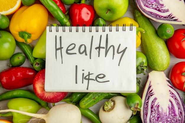 Vista dall'alto diverse verdure con frutta su sfondo bianco dieta insalata salute colore maturo