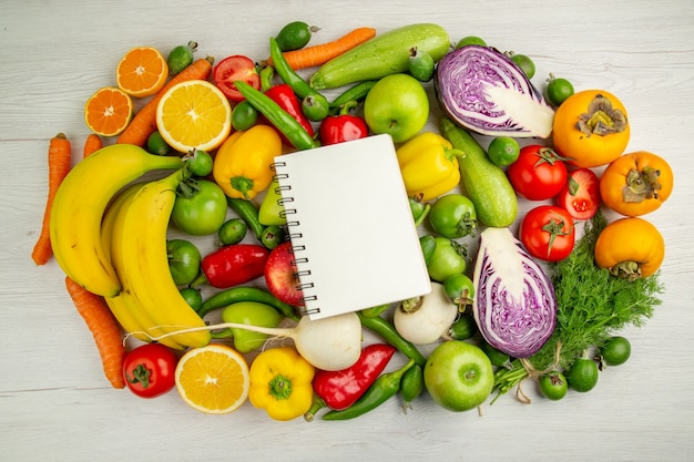 Vista dall'alto diverse verdure con frutta su sfondo bianco dieta insalata salute matura