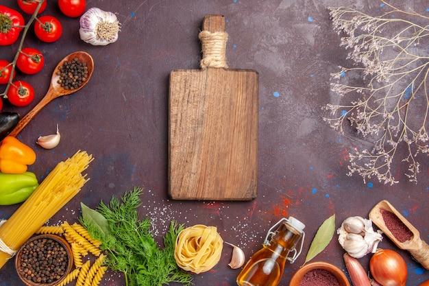 Top view different vegetables with seasonings on dark desk salad health vegetable meal food