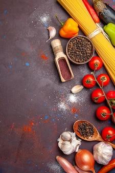 暗い背景の健康サラダ野菜に調味料とさまざまな野菜の上面図