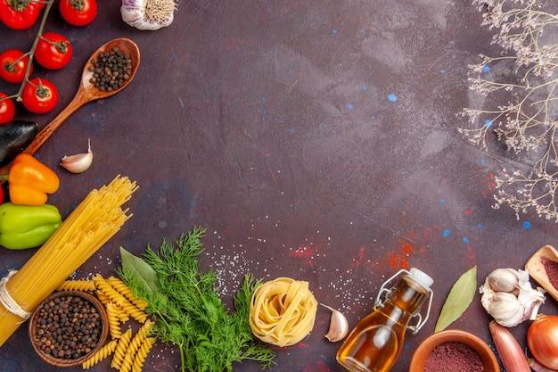 暗い背景の調味料とさまざまな野菜の上面図サラダ健康野菜ミール食品