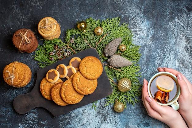 Vista dall'alto diversi deliziosi biscotti con una tazza di tè sul tavolo luminoso