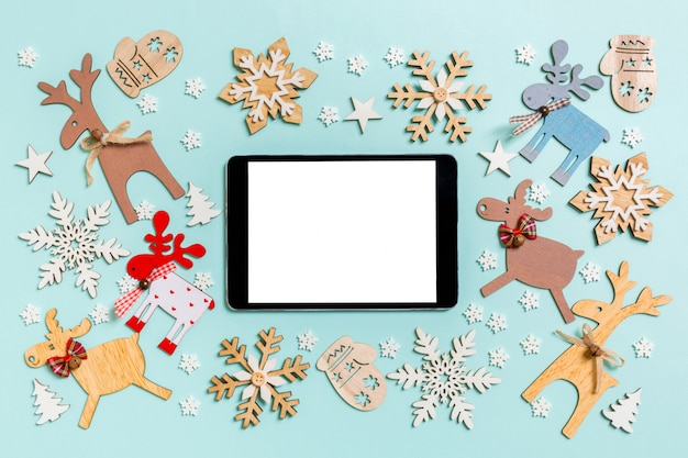 Top view of digital tablet on blue made of holiday decorations and toys.