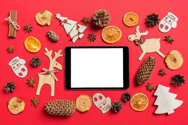 Top view of digital tablet, decorated with festive toys and christmas symbols reindeers and new year trees. holiday concept