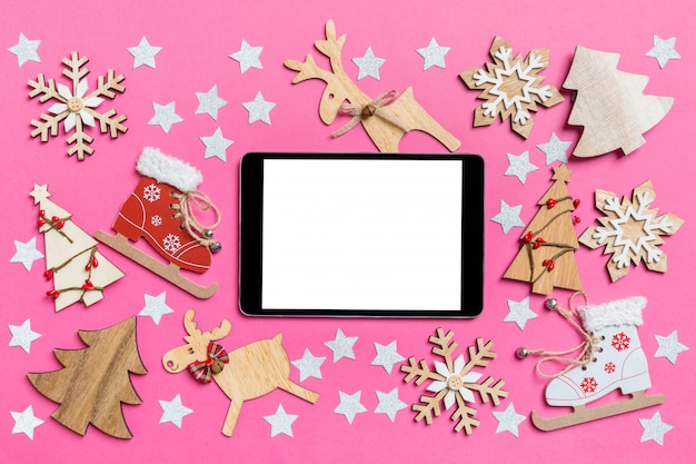 Top view of digital tablet, pink decorated with festive toys and christmas symbols reindeers and new year trees