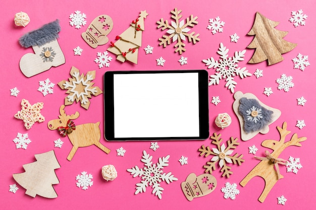 Top view of digital tablet on pink made of holiday decorations and toys.