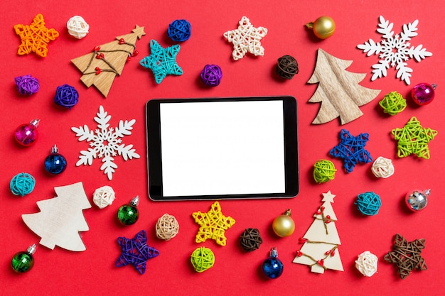 Top view of digital tablet on red made of holiday decorations and toys