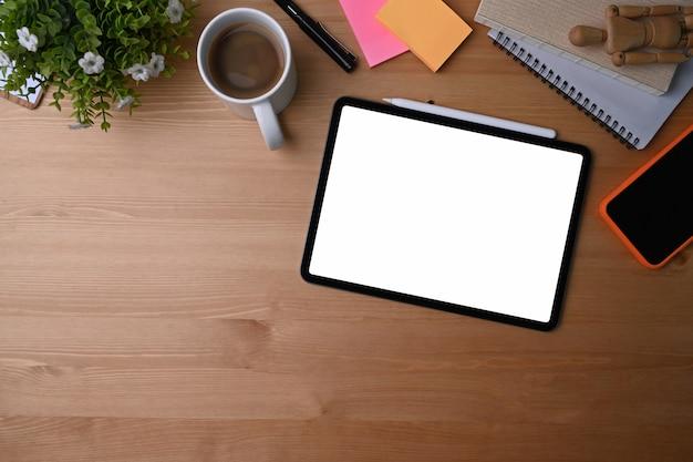 Цифровая таблетка, смартфон, кофейная чашка, комнатное растение и тетрадь взгляд сверху на деревянной предпосылке взгляд сверху.