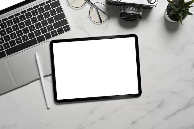 Вид сверху цифровой планшет, стилус и портативный компьютер на мраморном фоне.
